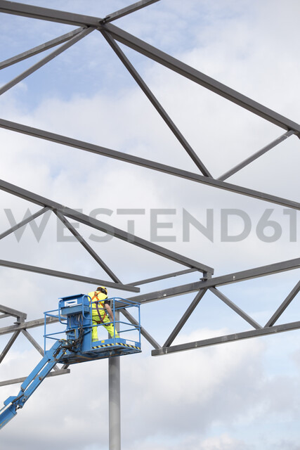Construction worker on cherry picker by building frame - FOLF10252