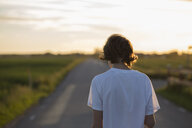 Teenage boy walking down a rural road in Laholm, Sweden - FOLF10255