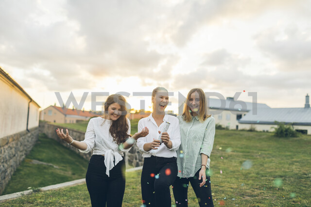 Three young woman using a confetti cannon outdoors in Karlskrona, Sweden - FOLF10291