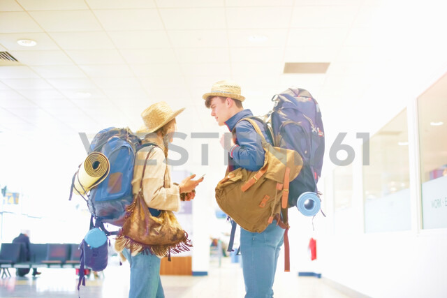 Young couple at airport, carrying backpacks, standing face to face, talking - ISF20121