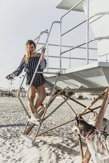 Young woman with pet dogs by lifeguard tower - ISF20133