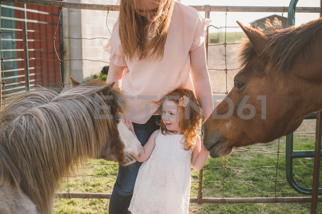 Mother and daughter petting pony in farm - ISF20142
