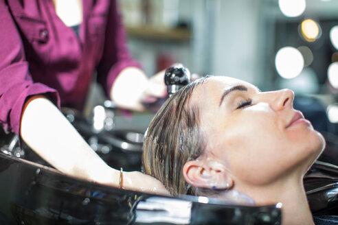 Hairdresser rinsing customer's hair in salon - ISF20145