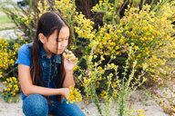 Girl kneeling to smell plant - ISF20169
