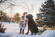 Female toddler with red hair playing in snow with dog, Keene, Ontario, Canada - ISF20187