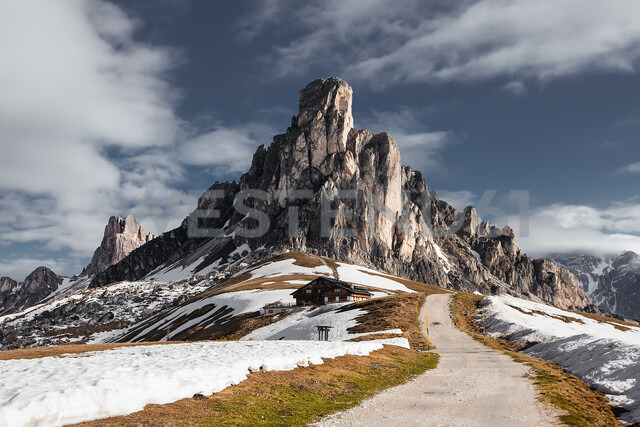 Dirt track in snow capped mountains, Dolomites, Italy - ISF20199