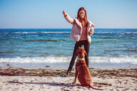 Mid adult woman on beach training her dog, Odessa, Odeska Oblast, Ukraine - ISF20208