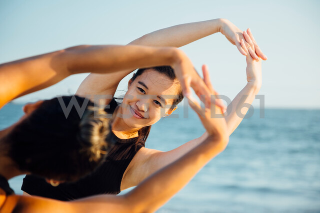Friends doing exercises on beach - ISF20217