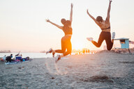 Friends jumping on beach, Long Beach, California, US - ISF20223