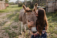 Woman kissing donkey - ISF20244