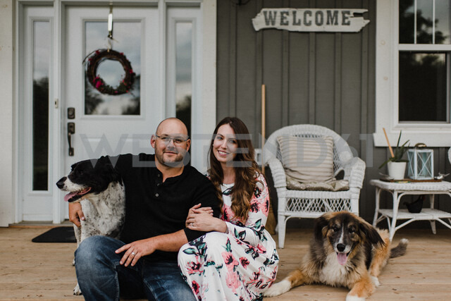 Couple and their two dogs sitting on porch - ISF20247