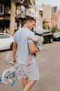Man carrying daughter on street - ISF20301