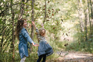 Sisters throwing leaves in air in forest - ISF20307