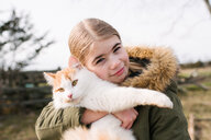 Girl cuddling cat in field - ISF20319