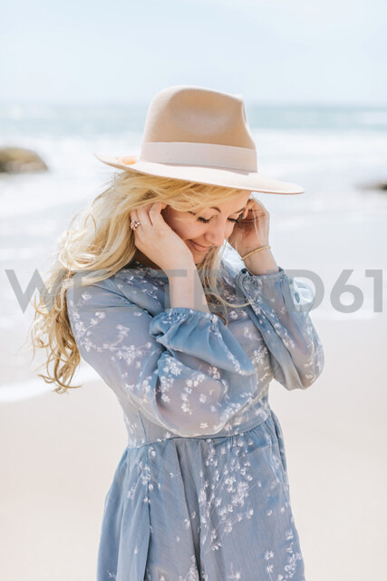 Young woman on windy beach with hands in hair, Menemsha, Martha's Vineyard, Massachusetts, USA - ISF20346
