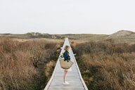 Lone young woman looking out from coastal dune boardwalk,  Menemsha, Martha's Vineyard, Massachusetts, USA - ISF20355