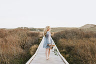 Young woman carrying bunch of flowers on coastal dune boardwalk,  Menemsha, Martha's Vineyard, Massachusetts, USA - ISF20358