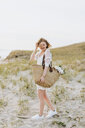 Young woman carrying shoulder bag with flowers on coastal dunes,  Menemsha, Martha's Vineyard, Massachusetts, USA - ISF20361