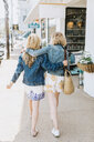 Two young female friends strolling along village sidewalk, rear view, Menemsha, Martha's Vineyard, Massachusetts, USA - ISF20364