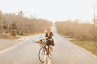 Young woman riding bicycle on rural road, Menemsha, Martha's Vineyard, Massachusetts, USA - ISF20367