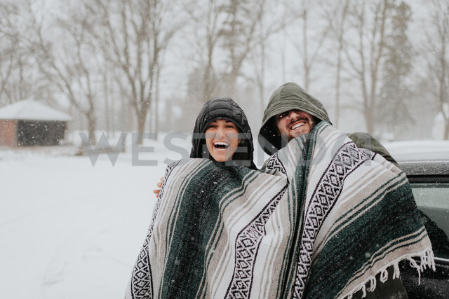 Couple wrapped in blanket in snowy landscape, Georgetown, Canada - ISF20370