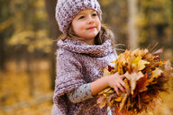 Little girl with handful of autumn leaves - ISF20394