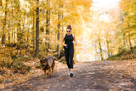 Woman jogging with dog in forest - ISF20409