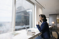 Pensive businesswoman at laptop looking out urban office window - HEROF05448