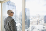 Pensive businessman looking at cityscape view at urban office window - HEROF05454