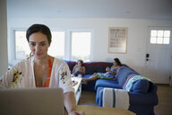 Mother using laptop with children on sofa in living room - HEROF05469
