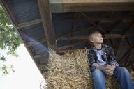 Pensive boy sitting on hay bale in barn - HEROF05520