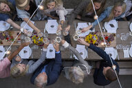 Overhead view friends toasting wine glasses at outdoor harvest dinner party - HEROF05556