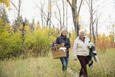 Mother and daughter carrying picnic basket and towel in autumn woods - HEROF05571