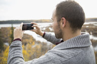 Man using camera phone at autumn lakeside - HEROF05574