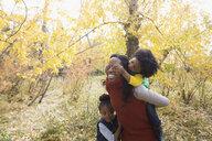Mother piggybacking daughter in autumn woods - HEROF05580