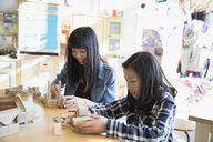 Mother and daughter playing with wooden pieces in science center - HEROF05640