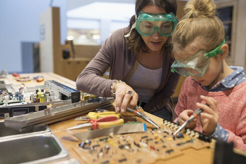 Mother and daughter assembling electronics in science center workshop - HEROF05655