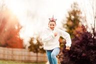 Girl with unicorn hairband running in park - ISF20466