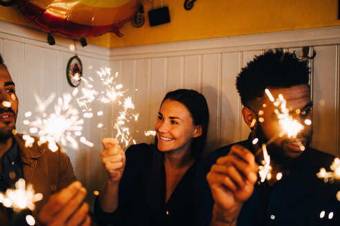 Smiling young woman with multi-ethnic male friends holding sparklers in restaurant during dinner party - MASF10878