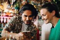 Smiling young man sharing smart phone with woman sitting in restaurant during brunch party - MASF10893