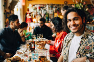 Portrait of smiling young man sitting with multi-ethnic friends enjoying dinner party at restaurant - MASF10905