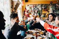 Young multi-ethnic friends enjoying while raising toast at table in restaurant - MASF10911