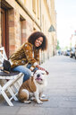 Smiling woman sitting with dog on sidewalk in city - MASF10926