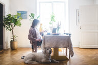 Dog sitting by woman having breakfast at table while working from home - MASF10935