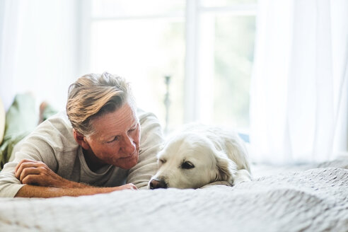 Close-up of senior man looking at cute dog while lying on bed in bedroom - MASF10944