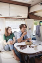 Smiling siblings relaxing at table in motor home during summer vacation - MASF10956