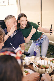 Teenage girl taking selfie with grandfather on mobile phone while having food at campsite - MASF10974