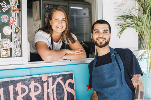 Portrait of smiling young male and female salesman at concession stand - MASF10986