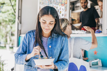Young woman eating fresh Tex-Mex in bowl against food truck - MASF10995
