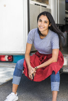 Portrait of confident young female owner sitting at food truck entrance - MASF11004